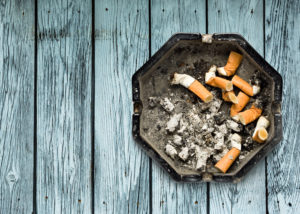 Ashtray of cigarette butts on light gray table