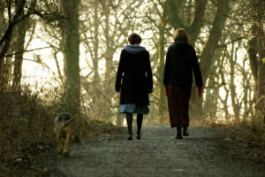 Rear view photo of two people in long skirts and cold-weather wear walking dog along forest path