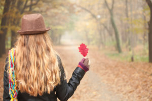Rear view of person with long hair and hat holding red leaf
