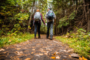 Couple hiking in mountains holds hands and walks together