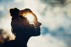 Double exposure image shows silhouette of person's head looking out among clouds with second exposure of clouds