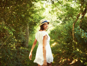Young adult wearing dress and matching summer hat stands on forest path looking back and smiling