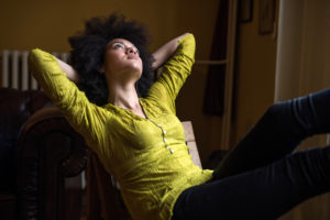 Young person with natural hair wearing green blouse leans back in chair, thoughtfully looking up