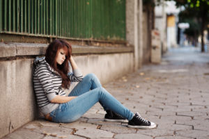 A girl in a striped hoodie sits on the sidewalk.