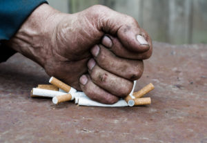 A fist crushes a pile of cigarettes.