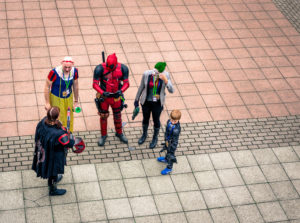 Five people in costumes form a semi-circle outdoors.