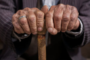 A close-up of two wrinkled hands holding a cane.