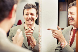 A mustached man winks and points at his reflection in a mirror.