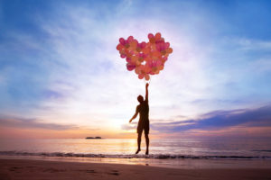 Person at beach holds heart-shaped bunch of balloons and rises slightly off ground