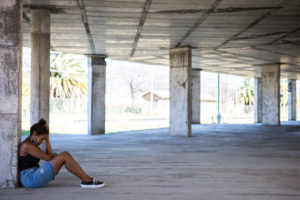 Teenager with hair in ponytail sits in stone building looking down alone