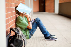 Teenager leans against brick wall with notebook open over face, backpack nearby