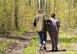 Rear view of parent and youth walking on trail in woods and talking