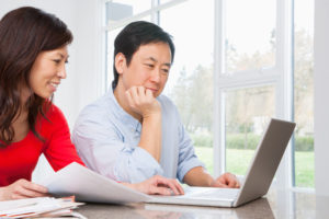 Adult couple sits at table working out finance plan with computer