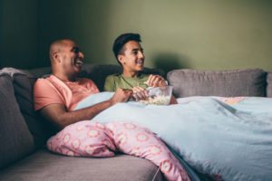 Father and teenager sit on sofa with popcorn in living room watching something on TV together