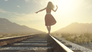 A girl balances on the rail of the train tracks. There are hills in the distance.