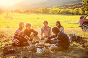 Group of friends sitting out in field camping, talking together