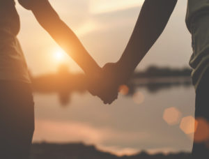 Close-up photo of loving couple holding hands while walking at sunset