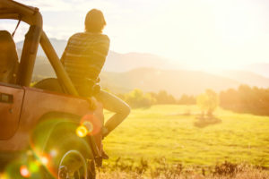 Rear view photo of young adult with short hair sitting on back of Jeep looking out at mountains and field