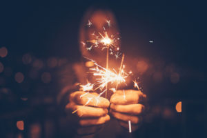 A close-up of sparklers in a man's hand. The man's face is out of focus.