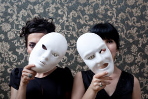 Two people with banks and hair pulled back looking out through masks held to side