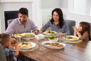 Two parents and two children sit down at the table to enjoy a meal together, talking and smiling