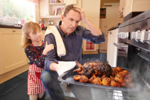 A man pulls a burnt turkey out of the oven. His daughter watches from behind his back.