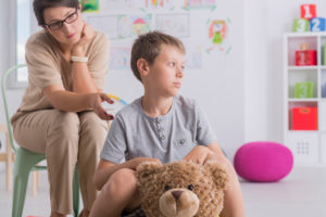 Adult sits with child in classroom or playroom. Child's expression is troubled, while adult's expression is encouraging