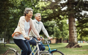 Older couple takes bike ride in tree-lined park. Both are smiling happily