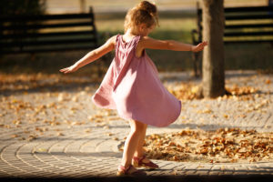 Child in pink dress dances outside among autumn leaves