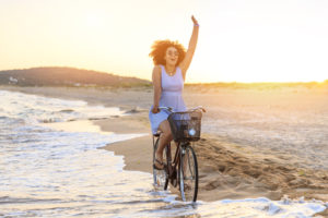 Person in sundress rides bike in waves at beach, waving at someone in distance