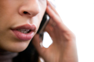Close up of young woman speaking over phone
