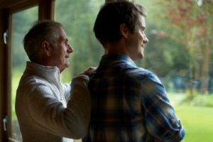Thoughtful parent and adult son stand at window of cottage and look out toward woods