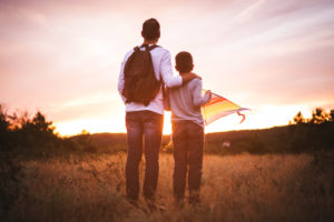 Rear view photo of father with arm around son's shoulders at sunset
