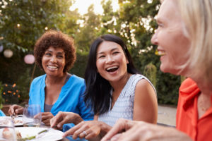 Three friends sit outside talking and laughing while eating in late afternoon