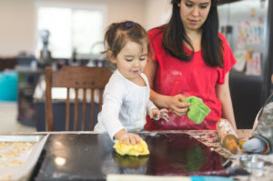 Parent stands back and watches child wipe down counter after baking
