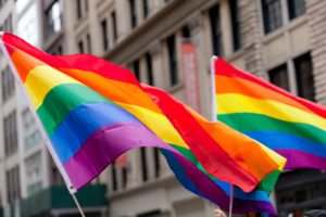 Two Pride flags fly on New York street during a Pride parade