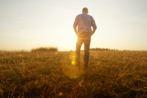 Rear view of person with short hair in pants and sweater walking in field at sunset