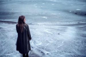 A woman stands alone on a frozen lake.