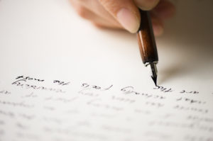 Close-up of a hand writing a letter with an old-fashioned pen.