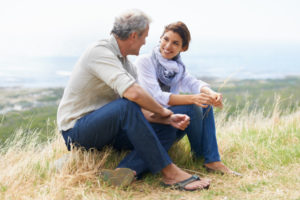 Mature adult couple sit on rock talking openly and smiling