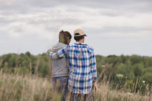 Rear view photo of two adults standing in field under cloudy sky. Person in flannel shirt and baseball cap has arm around person with long ponytail