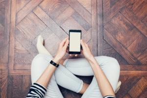Overhead view of person sitting on wood floor holding a smartphone