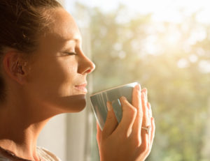Woman takes a moment to enjoy her coffee and the sunlight on her face.