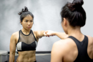 A woman in gym clothes touches her fist to her reflection.