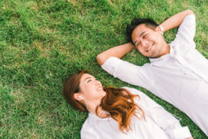 A young couple wearing white shirts lie side by side on spring grass.