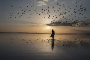 Woman walking on beach at sunrise surrounded by flying birds.