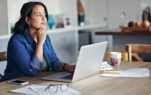 Woman sitting at computer, considering some options