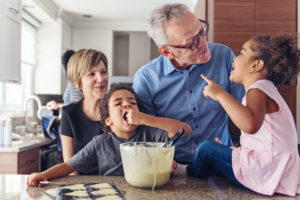 Two grandparents teach kids how to make cupcakes (while one kid taste tests the batter!).