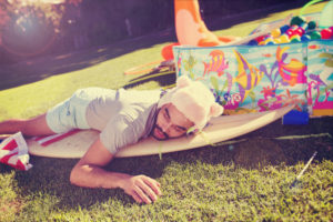 A grown man is passed out on the yard next to a kiddie pool.