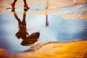 Reflection of woman walking with an umbrella in a puddle